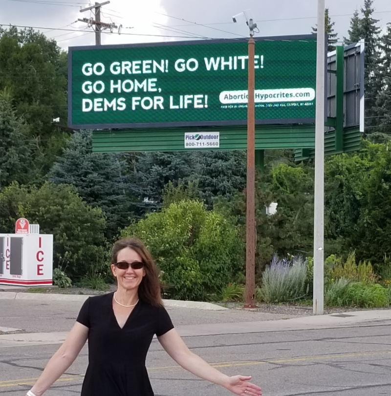 DFLA President Kristen Day smiling next to a billboard by Progress Michigan that says Go Green! Go White! Go home Dems for Life!