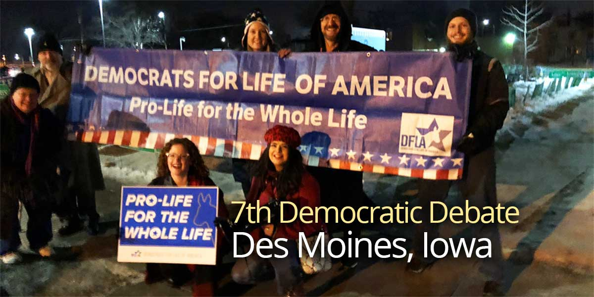 DFLA Iowa members at the 7th Democratic Debate in Des Moines, smiling and holding signs that say Pro Life for the Whole Life